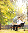 Businessperson on bench working on a laptop in a park young sitting wooden and shot with tilt and shift Stock Photo