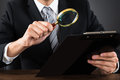 Businessperson Inspecting Document With Magnifying Glass Royalty Free Stock Photo