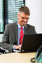 Businessperson with laptop in his business office Stock Photo