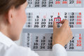 Businessperson marking on calendar close up of important date Stock Photos