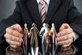 Businessperson Protecting Cutout Figures Royalty Free Stock Photo