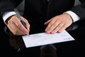Businessperson signing cheque close up of hands with pen Royalty Free Stock Photography