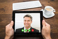 Businessperson video chatting with colleague close up of on digital tablet at desk Royalty Free Stock Images