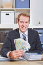 Businesss man with euro money fan smiling sitting in his office Stock Images