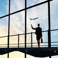 Businesswoman at airport image of looking airplane taking off Stock Photography