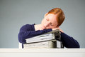 Businesswoman asleep at work a young caucasian sleeping on top of a stack of folders with documents or other paperwork Royalty Free Stock Photography