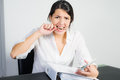 Businesswoman biting her pen in frustration with a distraught expression worry or anger as she sits at desk holding a Stock Photo