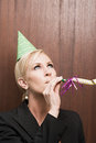 Businesswoman blowing party horn blower Royalty Free Stock Photo