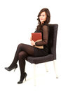 Businesswoman with book sitting on chair Royalty Free Stock Photos
