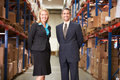 Businesswoman and businessman in distribution warehouse smiling to camera Royalty Free Stock Image