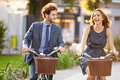 Businesswoman and businessman riding bike through city park close up of smiling Stock Image