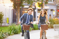 Businesswoman and businessman riding bike through city park fashioned smiling Royalty Free Stock Photo