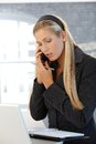 Businesswoman busy working young talking on mobile phone taking notes to personal calendar Royalty Free Stock Image