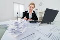 Businesswoman Calculating Invoice At Desk Royalty Free Stock Photo
