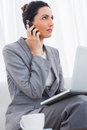 Businesswoman calling with her mobile phone and using laptop sit Royalty Free Stock Photo