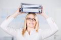 Businesswoman carrying two binders on head young blond in office Royalty Free Stock Image