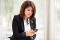 Businesswoman with a cell phone pretty hispanic social networking her Royalty Free Stock Images