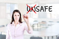 Businesswoman choosing Safe instead of Unsafe. Office background. Royalty Free Stock Photo