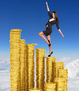 Businesswoman climbing stairs of gold coins Royalty Free Stock Photo