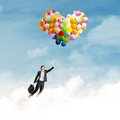 Businesswoman with colorful balloons young and flying over clouds Royalty Free Stock Photos