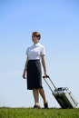 Businesswoman in contemplation holding luggage in park Stock Photos