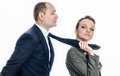 Businesswoman in control of a man woman sexy women holding her men by his tie dominating him Royalty Free Stock Photo