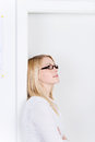 Businesswoman day dreaming while leaning on door side view of young frame Stock Images