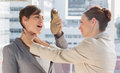 Businesswoman defending herself from her colleague strangling her in a bright office Royalty Free Stock Images