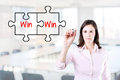 Businesswoman drawing a Win Win Puzzle Concept on the virtual screen. Office background. Royalty Free Stock Photo