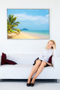 Businesswoman dreams cute legs sitting on sofa and dream about vacation Royalty Free Stock Image