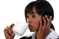 Businesswoman drinking coffee whilst telephoning Stock Photos