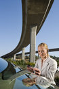 Businesswoman with earpiece using electronic organiser by car beneath overpass Royalty Free Stock Photos