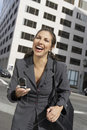 Businesswoman enjoying conversation on mobile phone outdoors cheerful a city street Royalty Free Stock Image