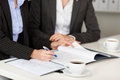 Businesswoman explaining documents to female coworker at desk midsection of office Stock Image