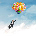 Businesswoman flying with balloons young holding colorful and over clouds Royalty Free Stock Photo