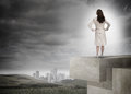 Businesswoman in front of cloudy sky and landscape with buildings rear view a brunette Stock Photo