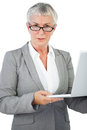 Businesswoman with glasses holding her laptop on white background Royalty Free Stock Photography