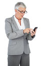 Businesswoman with glasses texting a message on her mobile phone Royalty Free Stock Photo