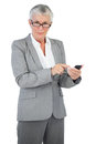 Businesswoman with glasses using her mobile phone on white background Royalty Free Stock Image