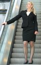 Businesswoman going down escalator portrait of a Royalty Free Stock Image