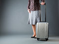 Businesswoman with a gray suitcase casually dressed on wheels over background Stock Photos
