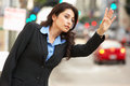 Businesswoman hailing taxi in busy street on sidewalk Royalty Free Stock Image