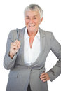 Businesswoman with hand on hip holding pen white background Royalty Free Stock Photo