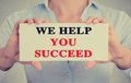 Businesswoman hands holding sign we help you succeed Royalty Free Stock Photo