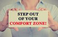 Businesswoman hands sign with step out of your comfort zone message holding white card text isolated on grey wall office Stock Images
