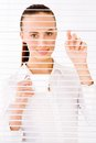 Businesswoman happy business woman peeking through a venetian blind in an office Stock Images