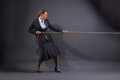 Businesswoman hauling at a rope isolated on dark grey background lady in business suit ready to fight for her position Royalty Free Stock Image
