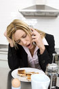 Businesswoman having breakfast in the kitchen and talking on the phone Royalty Free Stock Photo
