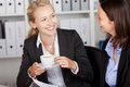 Businesswoman having coffee while looking at coworker happy young in office Stock Photos