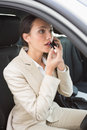 Businesswoman having a phone call while putting on lipstick Royalty Free Stock Photo